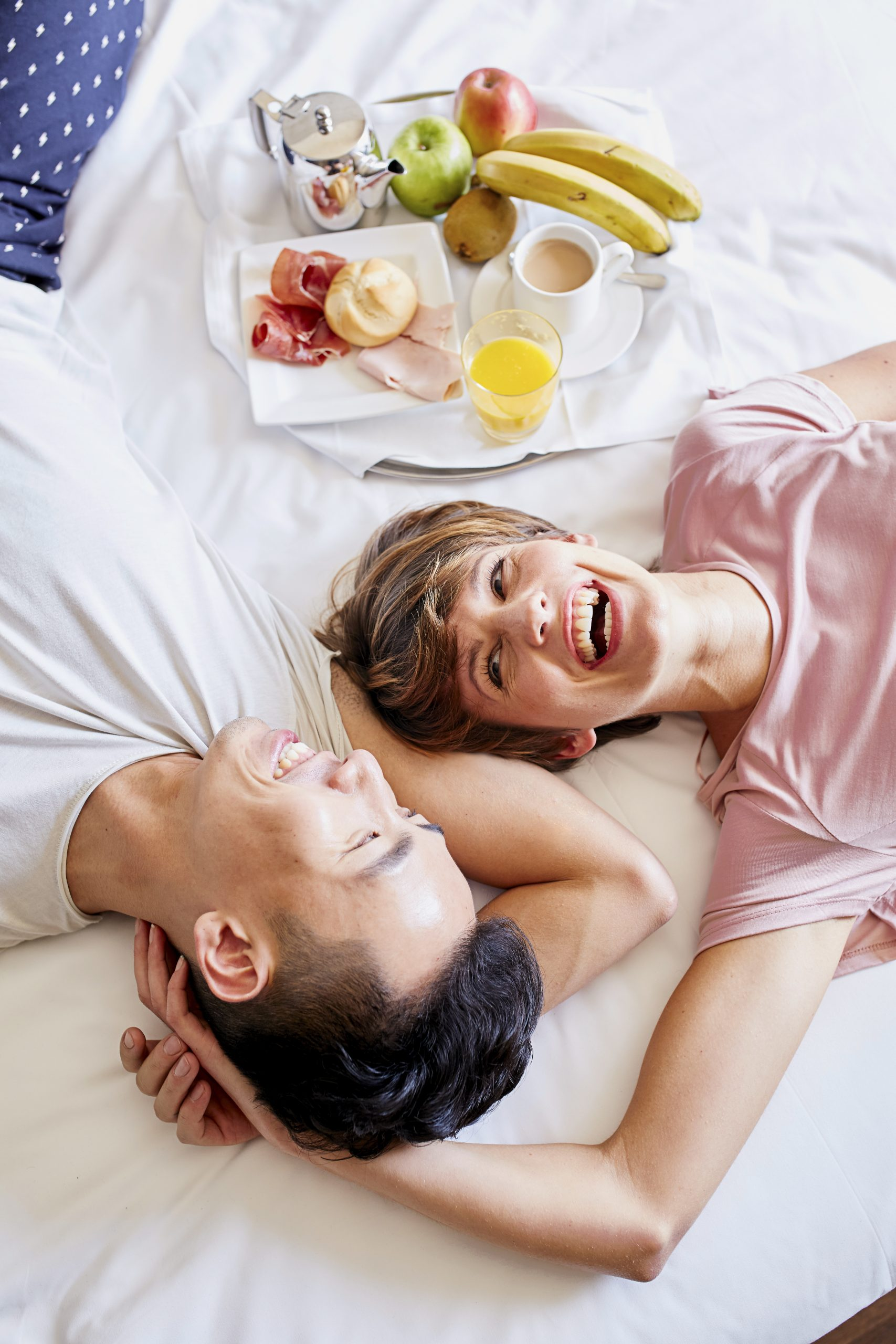 Happy Couple Lying By Breakfast Tray On Bed